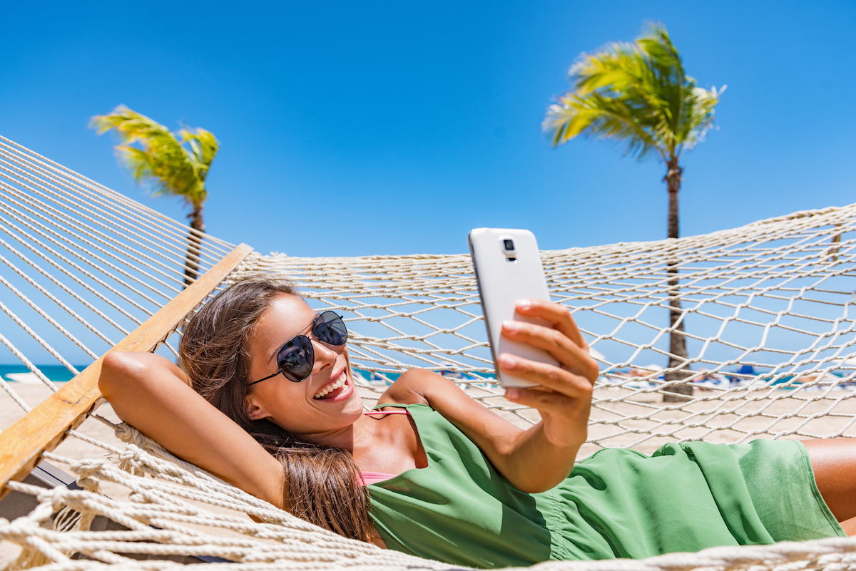 Woman on a beach hammock taking a selfie