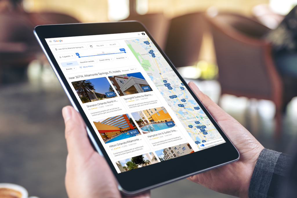 Person holding ipad with Google Hotel Local Search Results