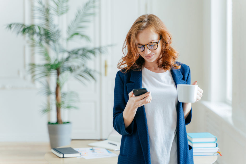 Successful Female Ceo Reads Notification On Modern Cell Phone, Has Coffee Break, Dressed In Formal C