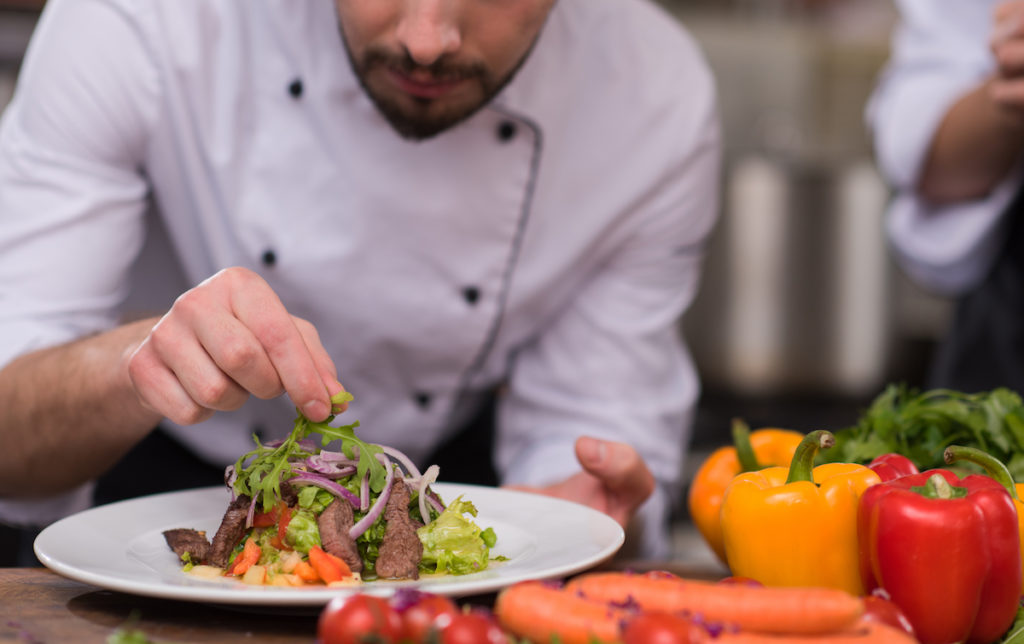 chef decorating garnishing prepared meal dish on the plate in restaurant