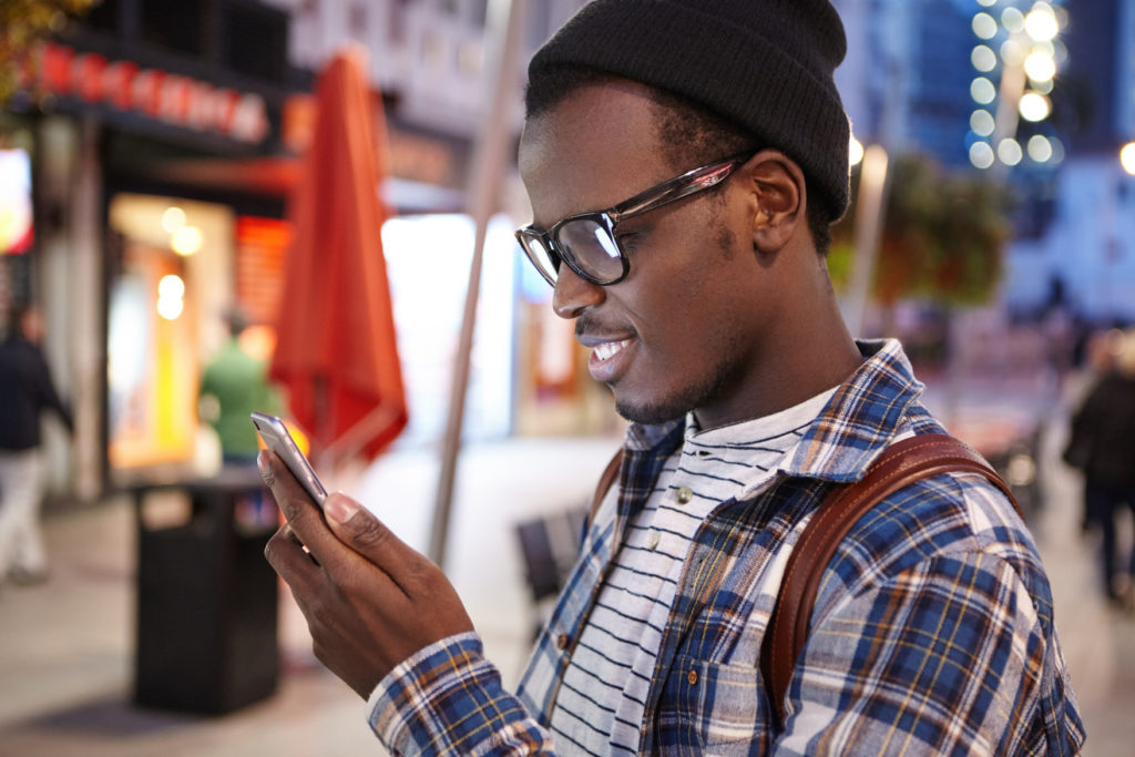 Young Man in Warm Clothes Looking at his Phone While Shopping