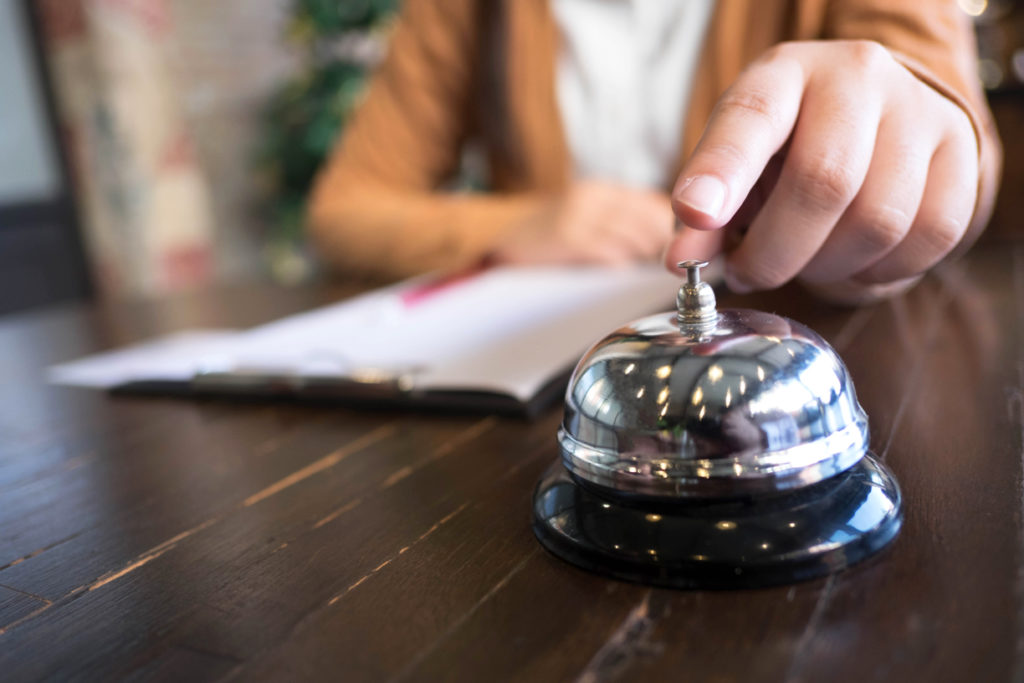 Women call hotel reception with finger push a bell in lobby hotel.