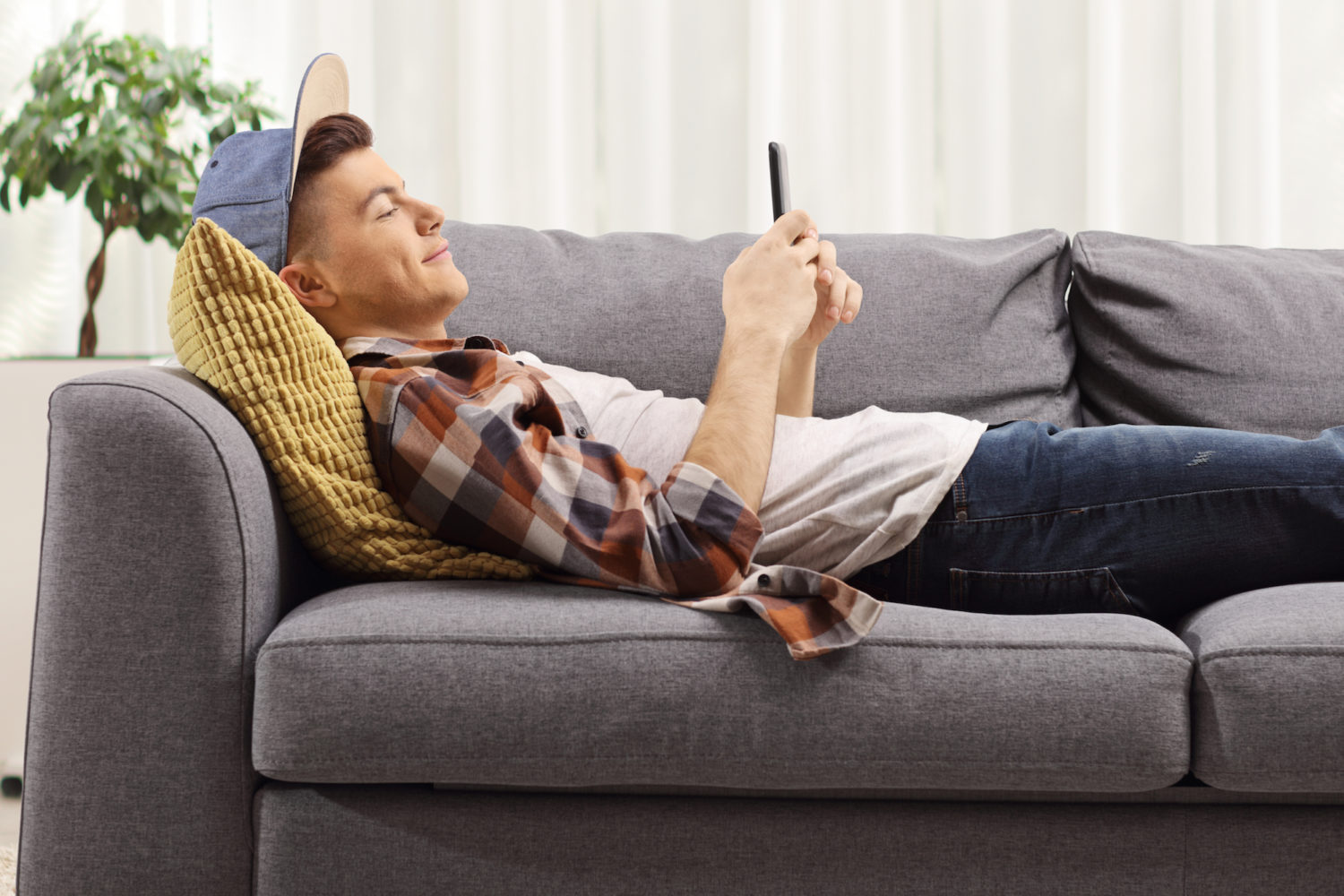 Young guy lying on a sofa and looking at a mobile phone at home