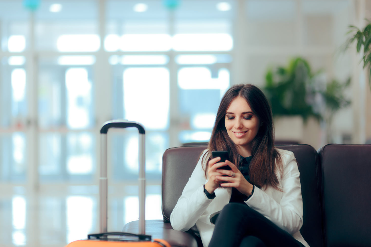 Woman sitting reading her phone in an airport terminal