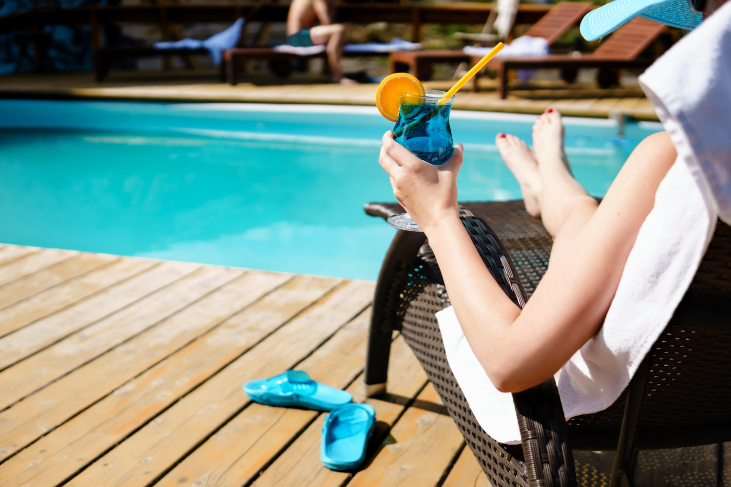 woman relaxing at poolside with a blue drink in hand