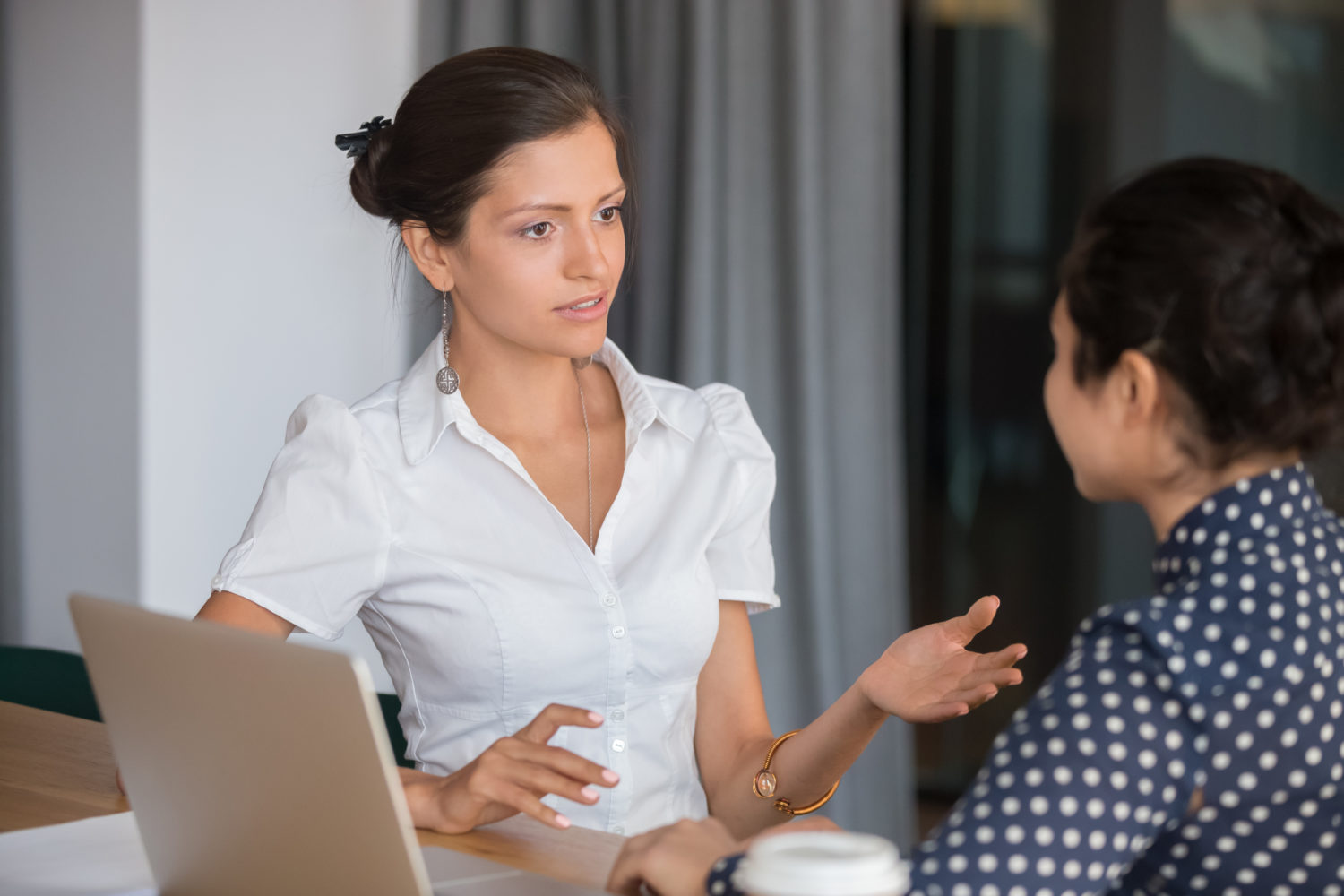 Female manager talking to employee with serious expression