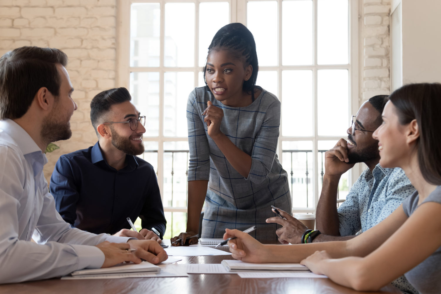 Female black executive talking to diverse employees at office briefing