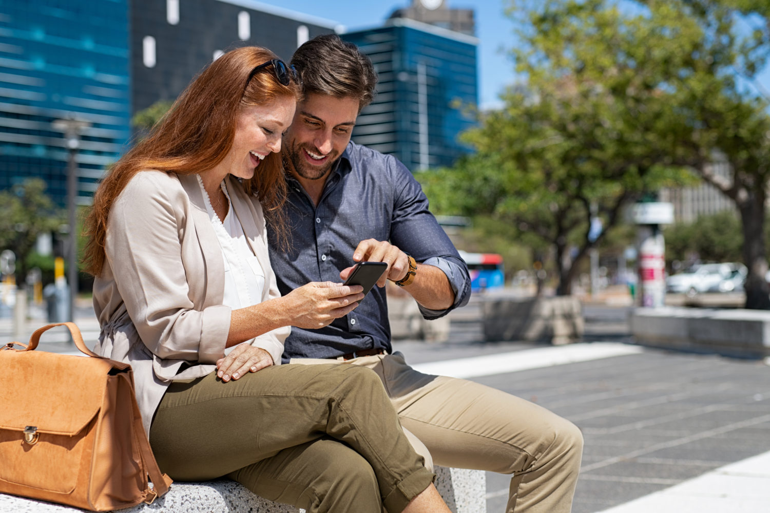Red-haired woman and man looking excitedly at a phone