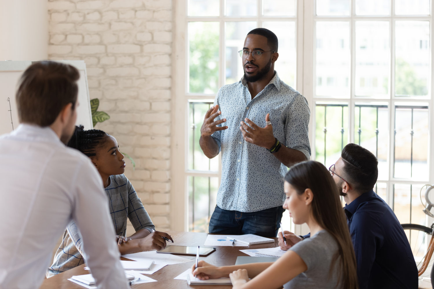 Black manager speaks to table of employees