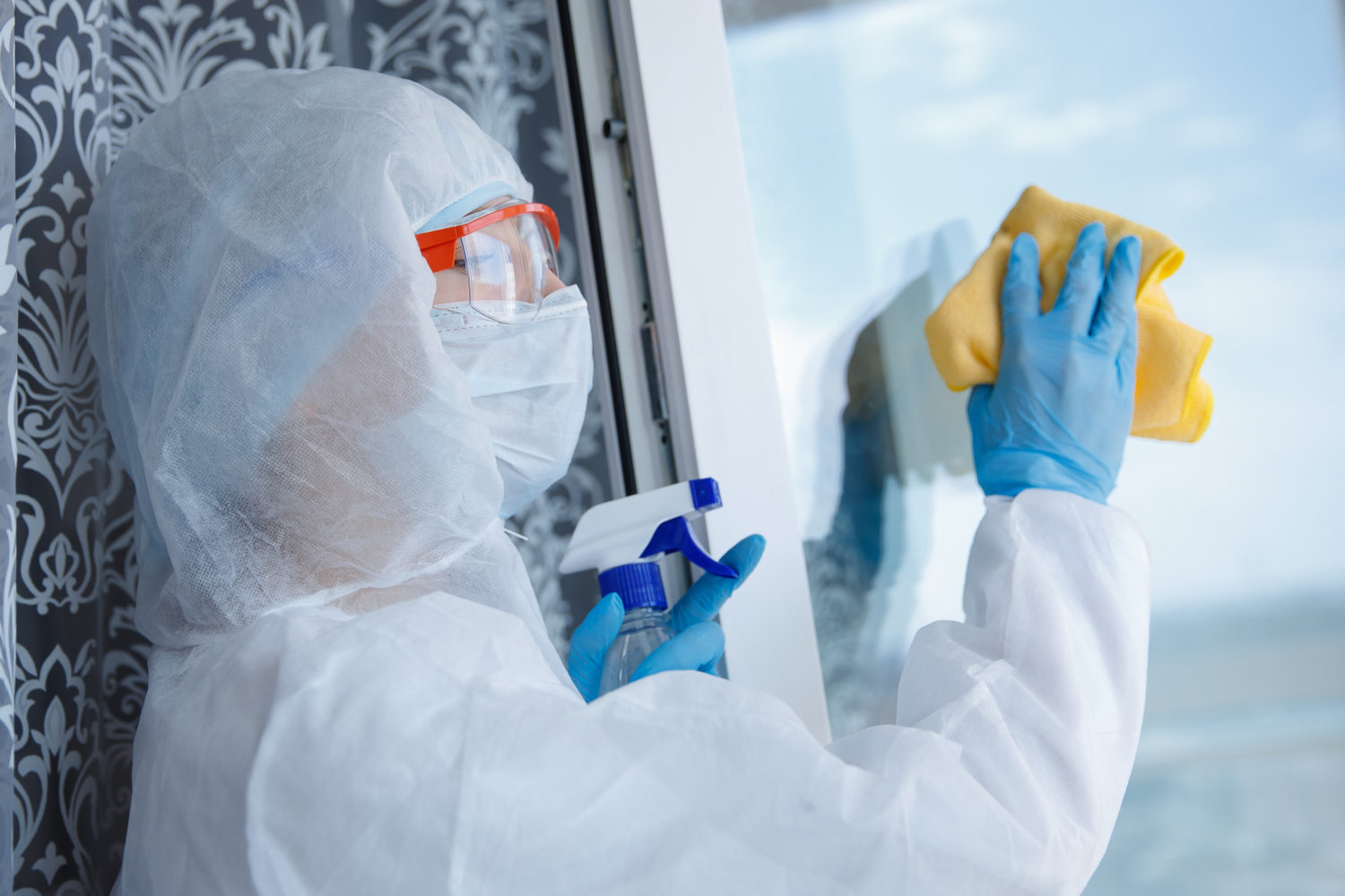 Woman wearing protective biohazard gear cleaning a window