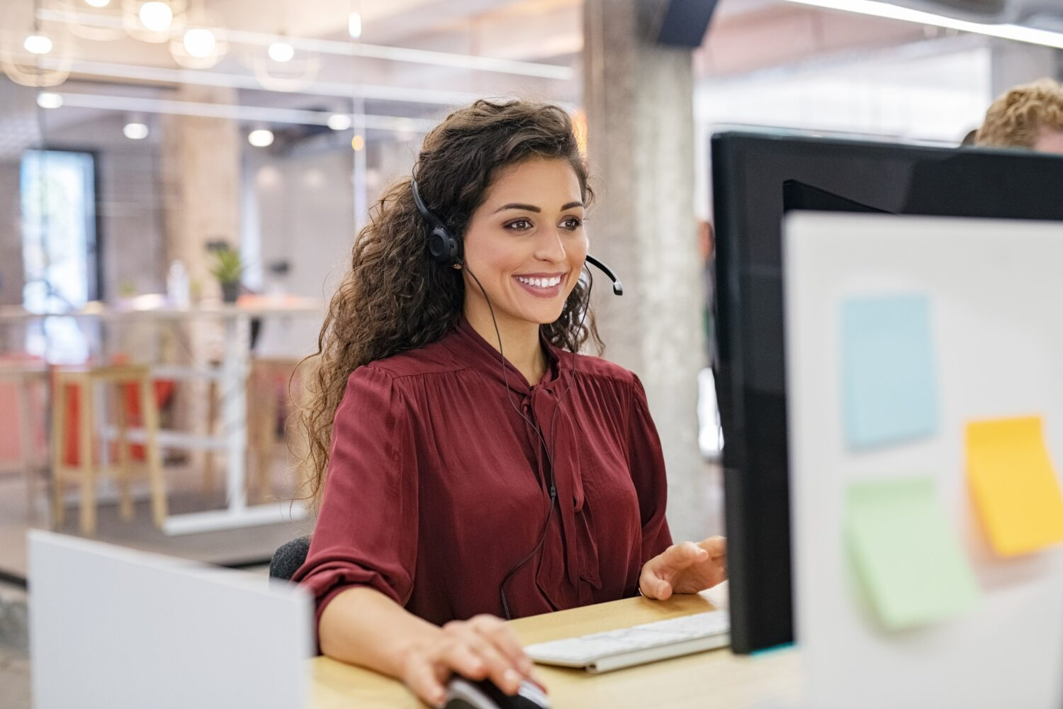 woman facing her computer wearing a headset and smiling