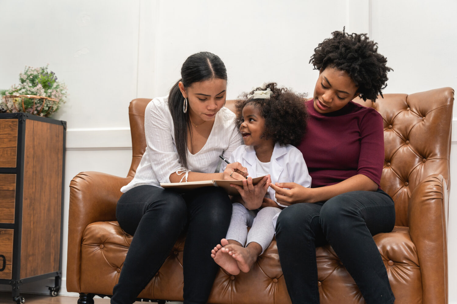 black lesbian mothers write in a notebook with their daughter between them