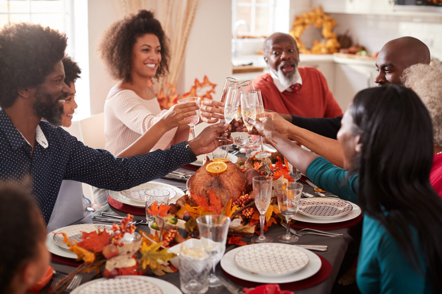 a large black family sits around a table and cheers glasses together