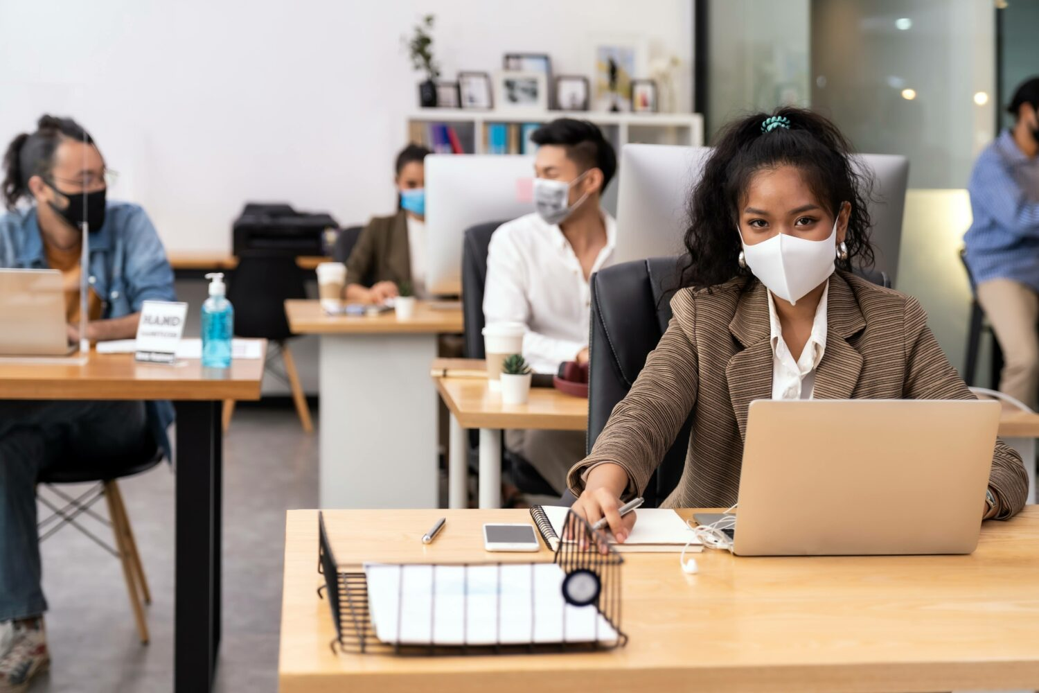 team members working distanced and masked in an office at laptops