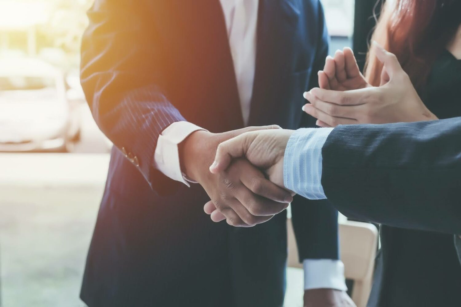 businesspeople wearing suits and shaking hands
