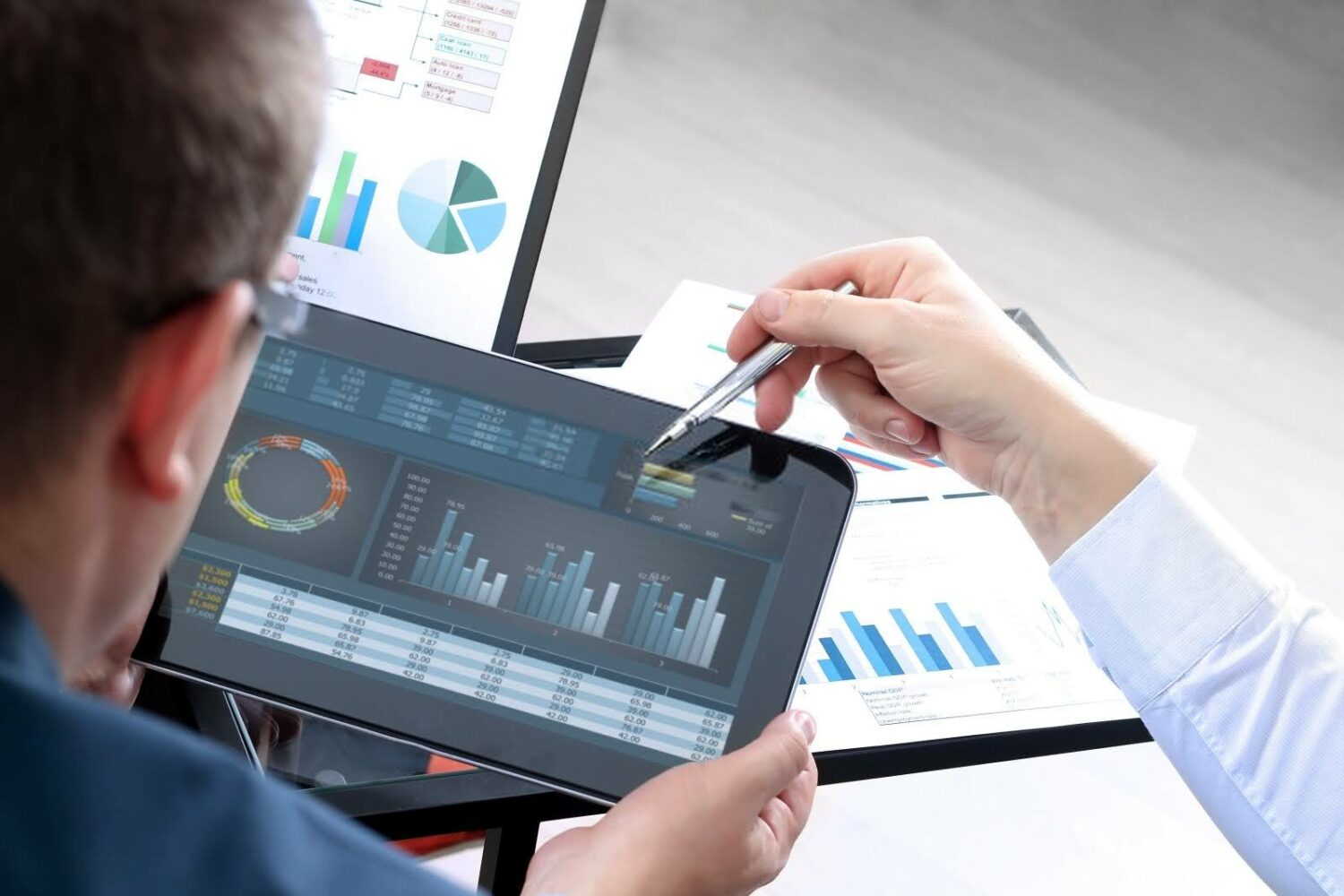 businessmen reviewing a tablet with graphs and charts on the screen