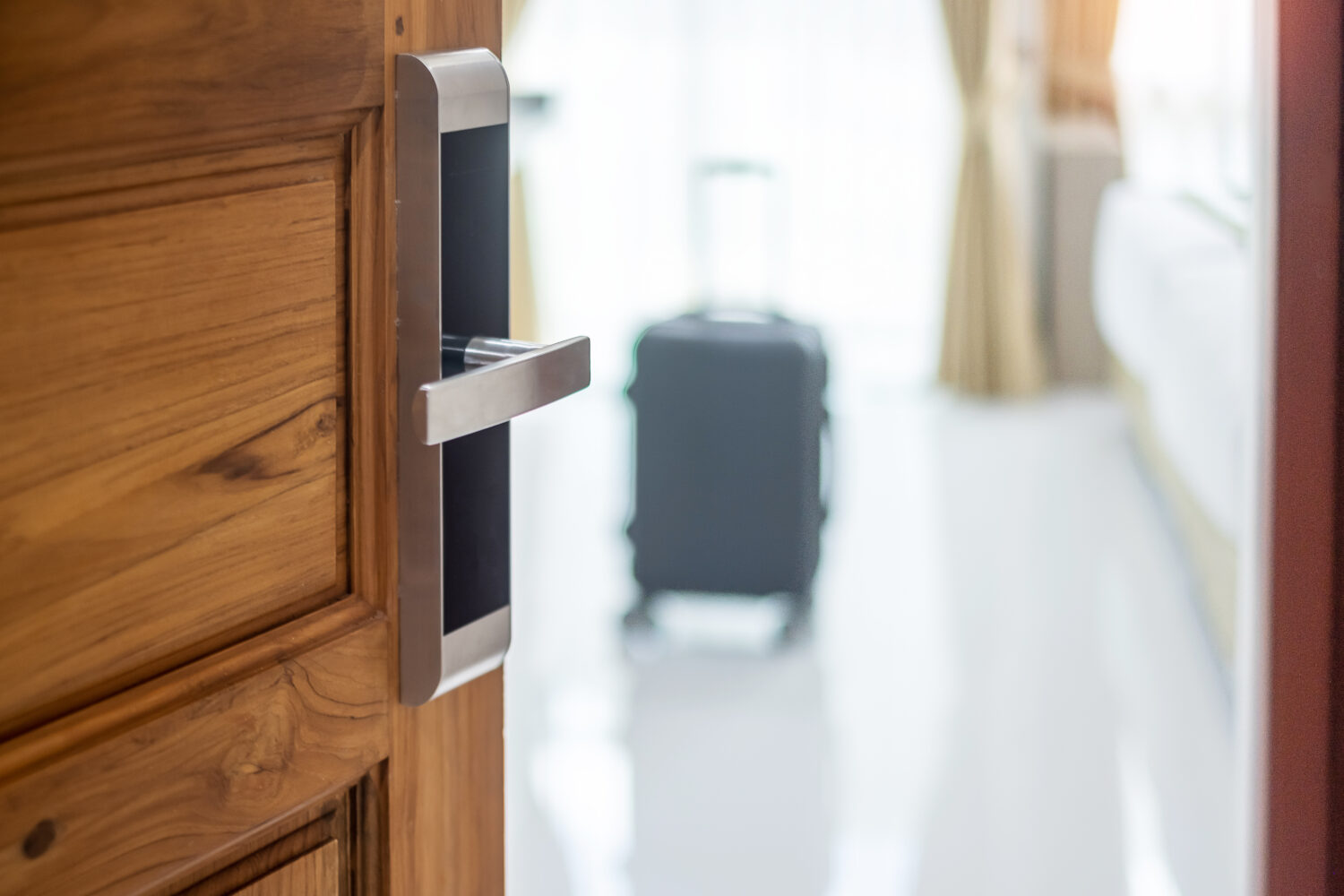 hotel door open to reveal a suitcase inside the room