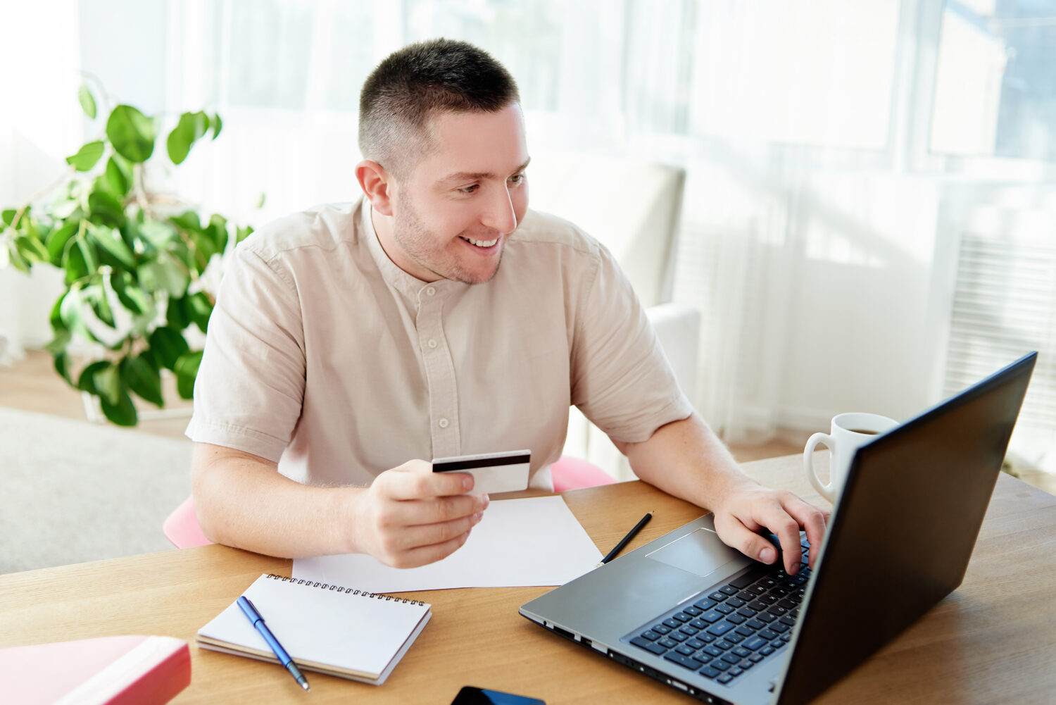 man looking at his laptop holding a credit card