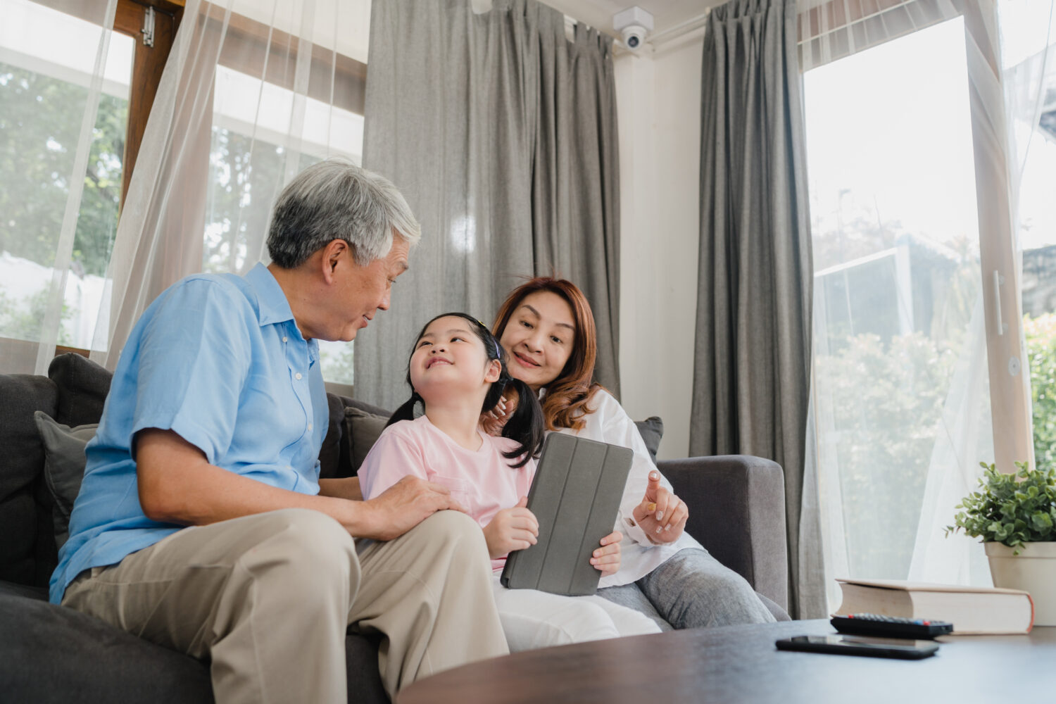 asian grandparents browsing social media with their young granddaughter