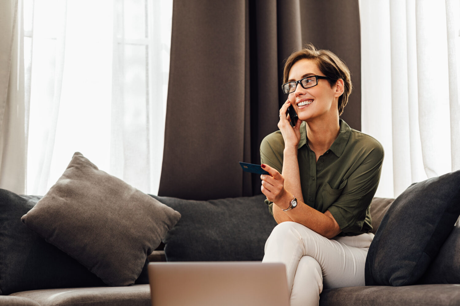 woman with short brown hair speaking on her phone in a hotel room