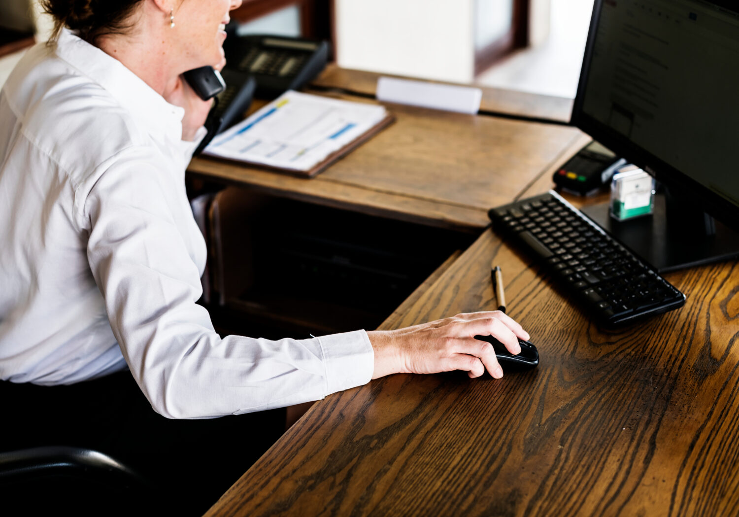 woman using a computer and on the phone at a reception desk