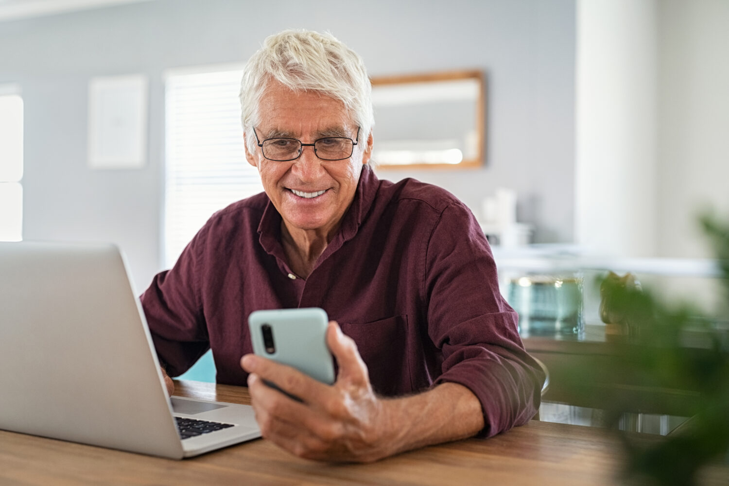 older male working at a laptop and smiling down at his phone