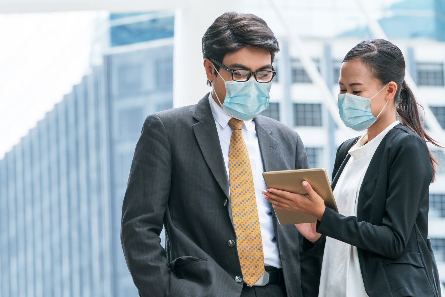 businessman and businesswoman wearing surgical masks discussing over a tablet