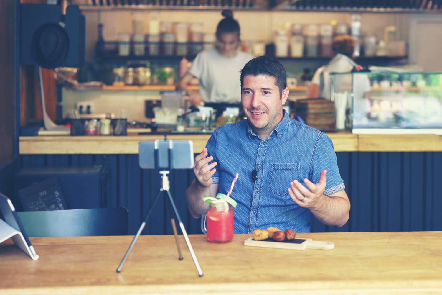 man with blue shirt recording himself using a tripod and camera at a restaurant