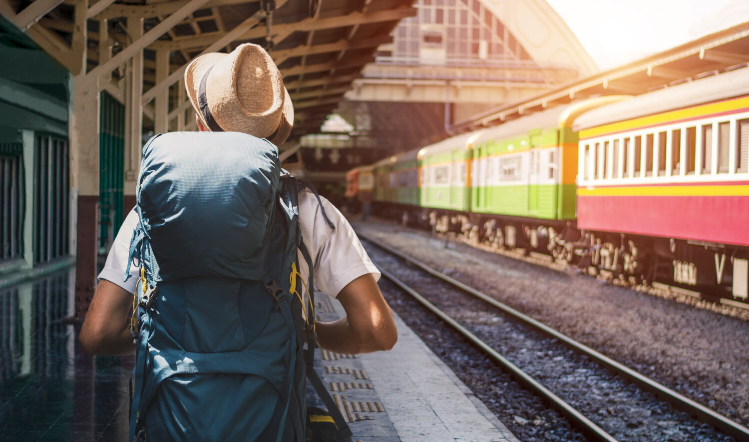 back of a man wearing a backpack and hat waiting for a train