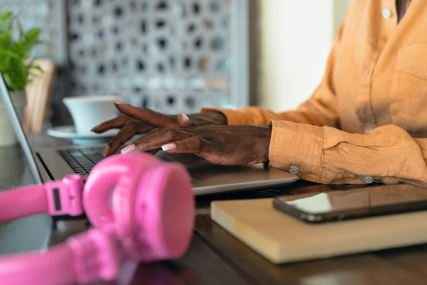 cropped photo of african american woman typing on her computer with pink headphones nearby