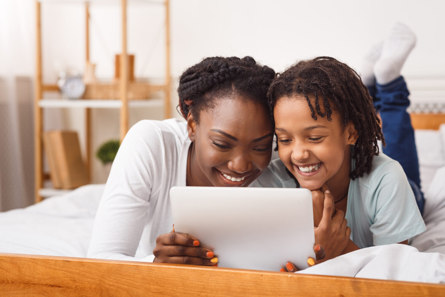 black mother and daughter laying in bed and smiling at a white tablet