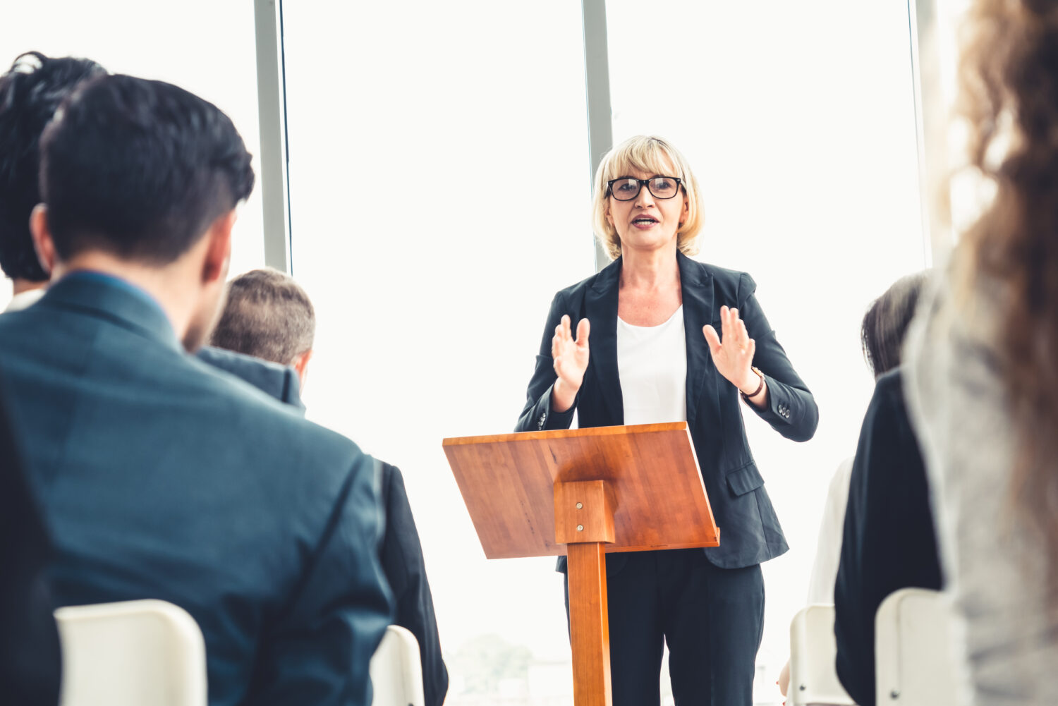 a blonde female stands at a podium and presents to businesspeople
