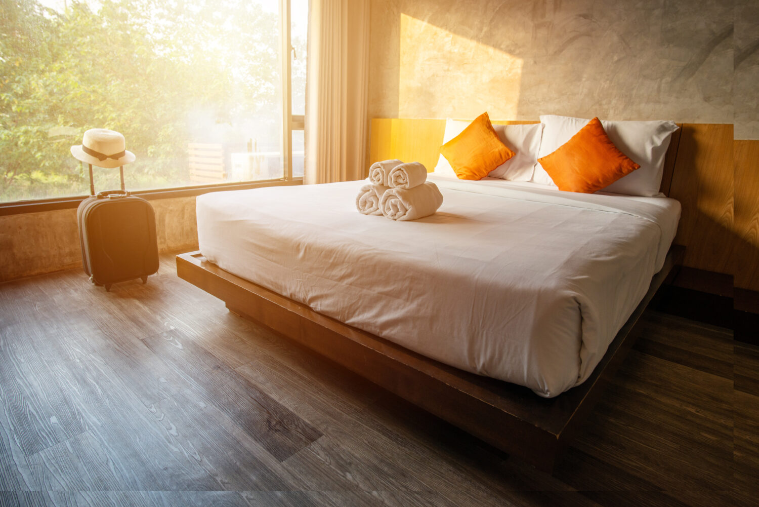a double bed with four pillows, two of which are orange