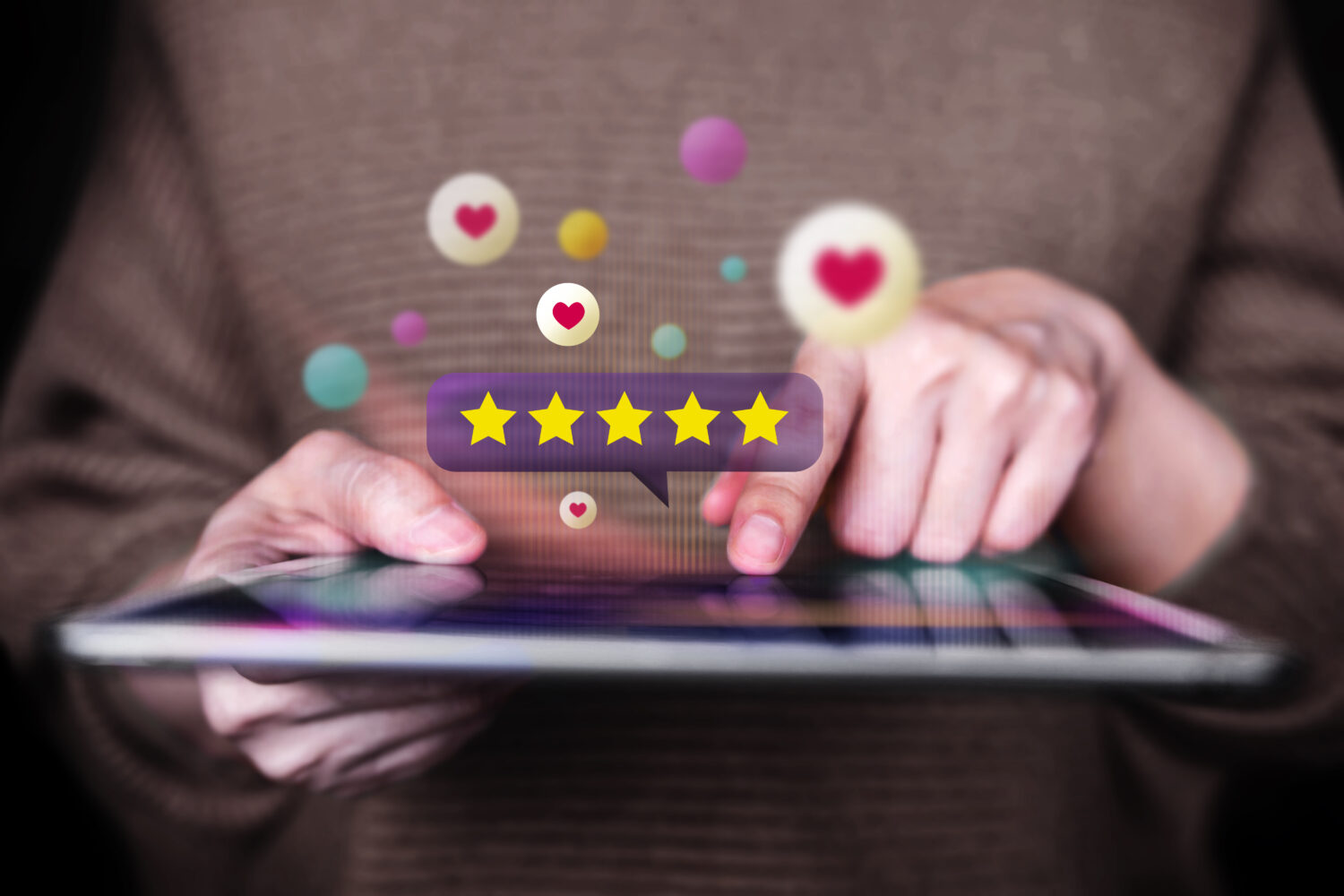 cropped image of hands using a tablet with floating star rating and hearts around