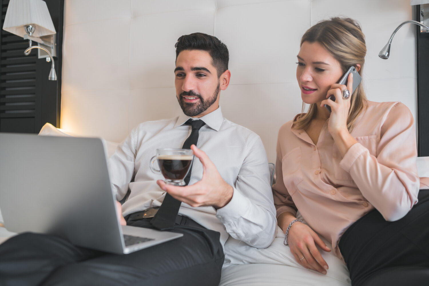 two young business people sitting on a bed and looking at a laptop together
