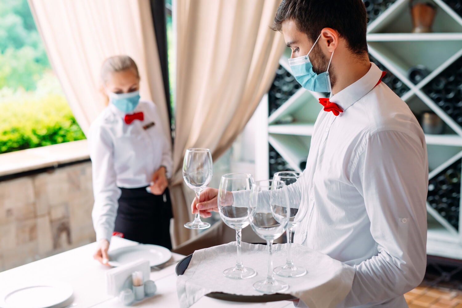 a waiter and his supervisor set a table with wine glasses