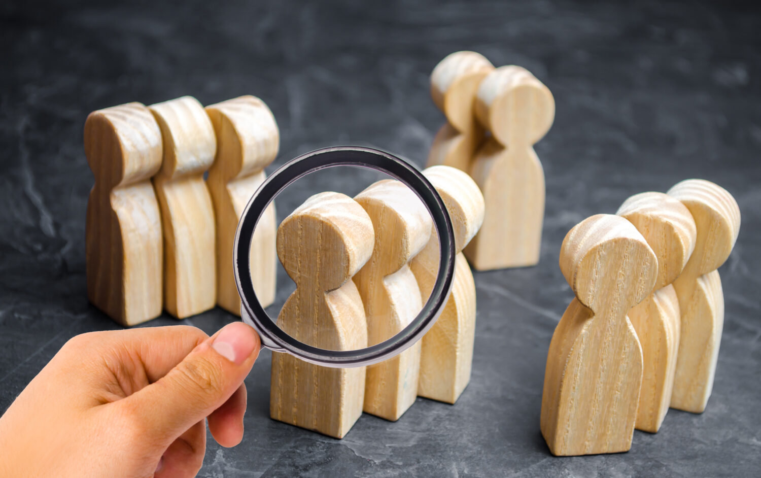 groups of wooden people with a hand holding a magnifying glass to look at them