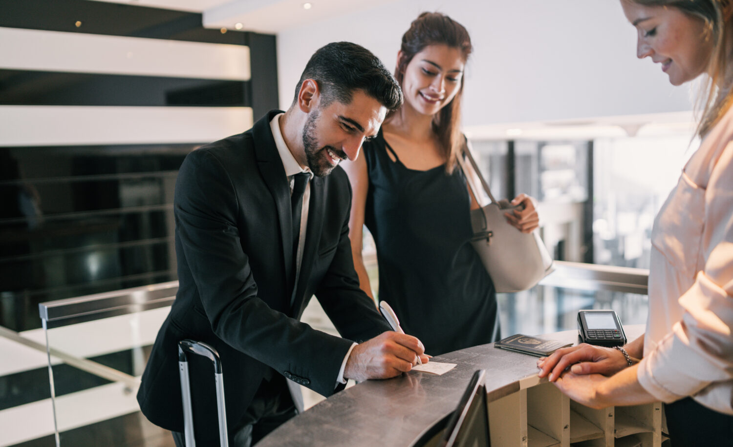 portrait of two young business people filling out a check-out survey