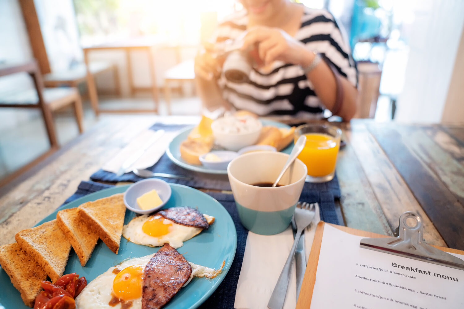 cropped photo of woman eating breakfast at a hotel restaurant