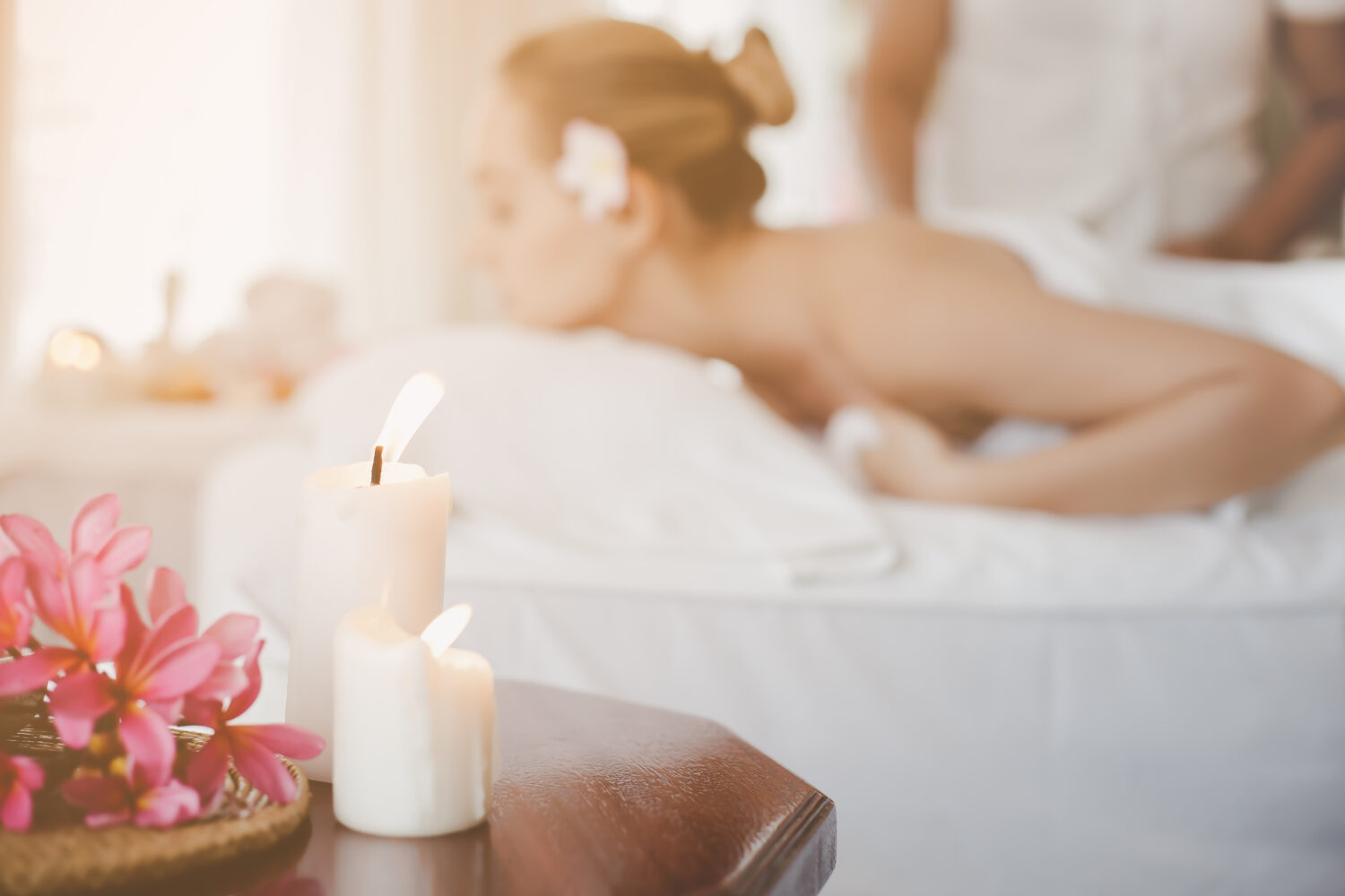 foreground candles on a table and a woman getting a massage in the background