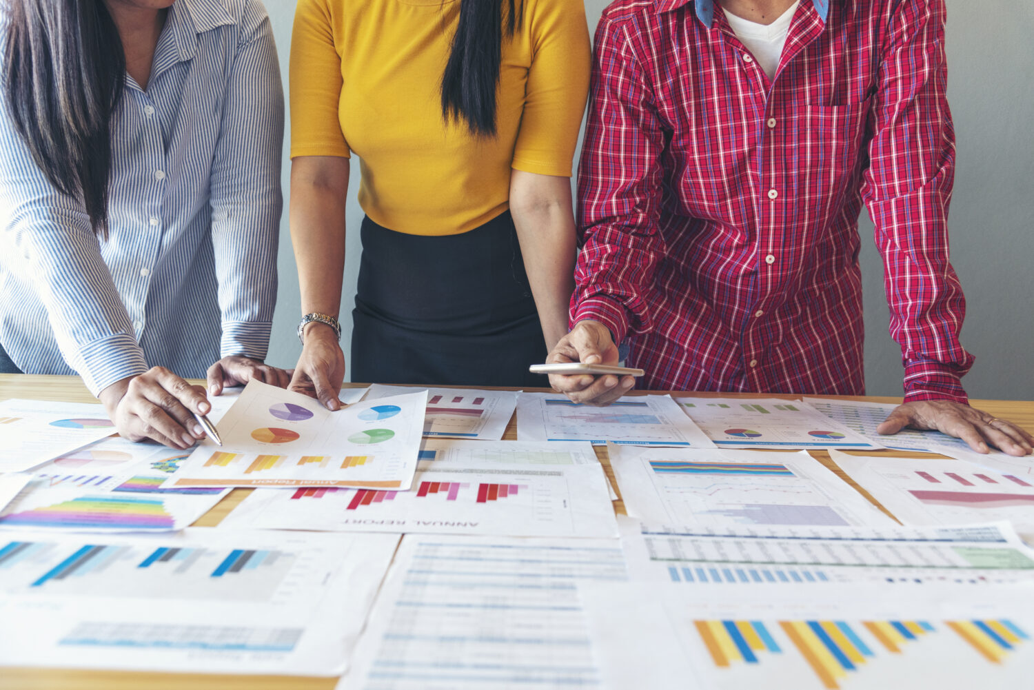 three people standing over a table covered in business charts and graphs