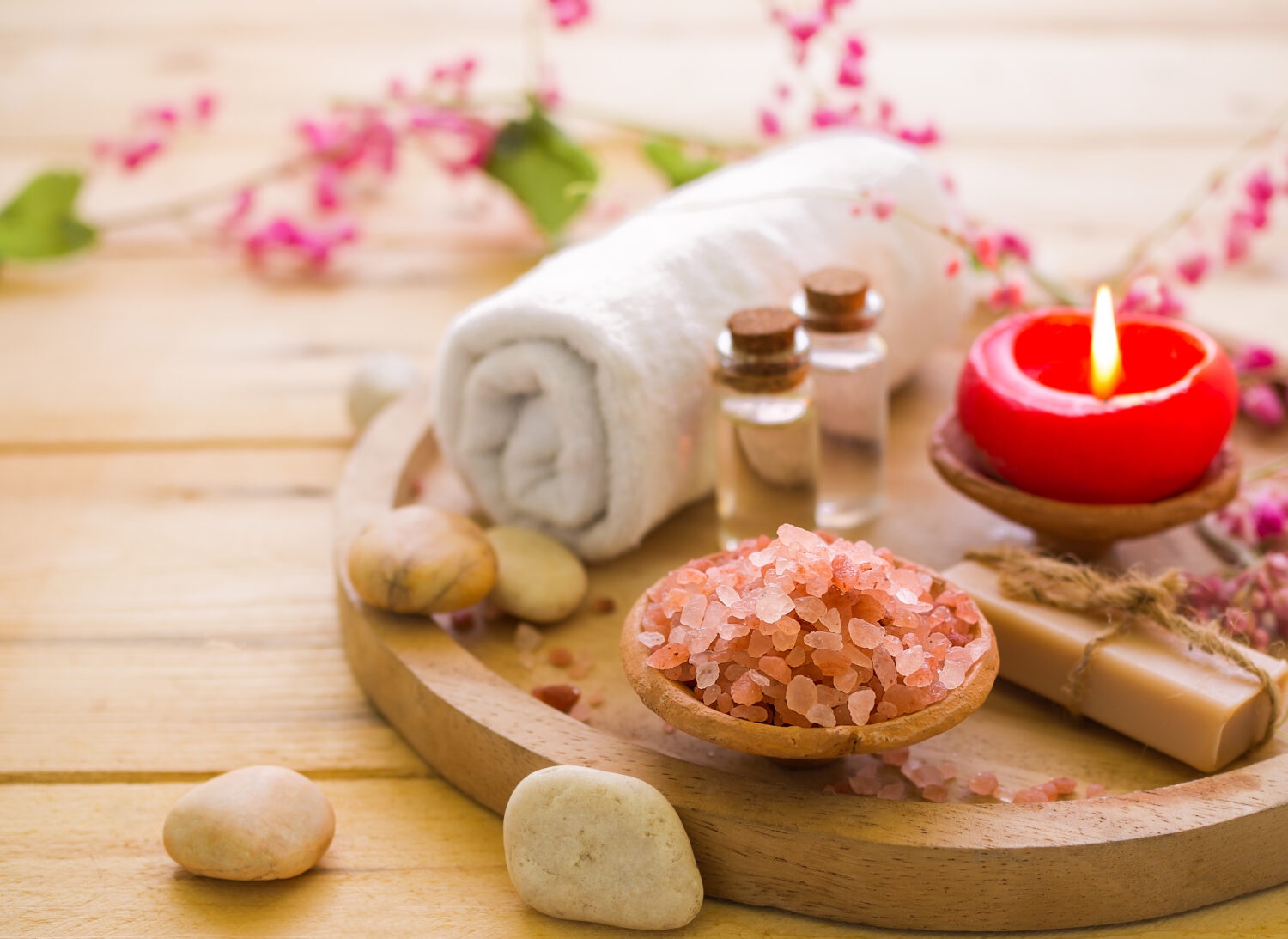aromatherapy set sitting on a wooden table surrounded by flowers