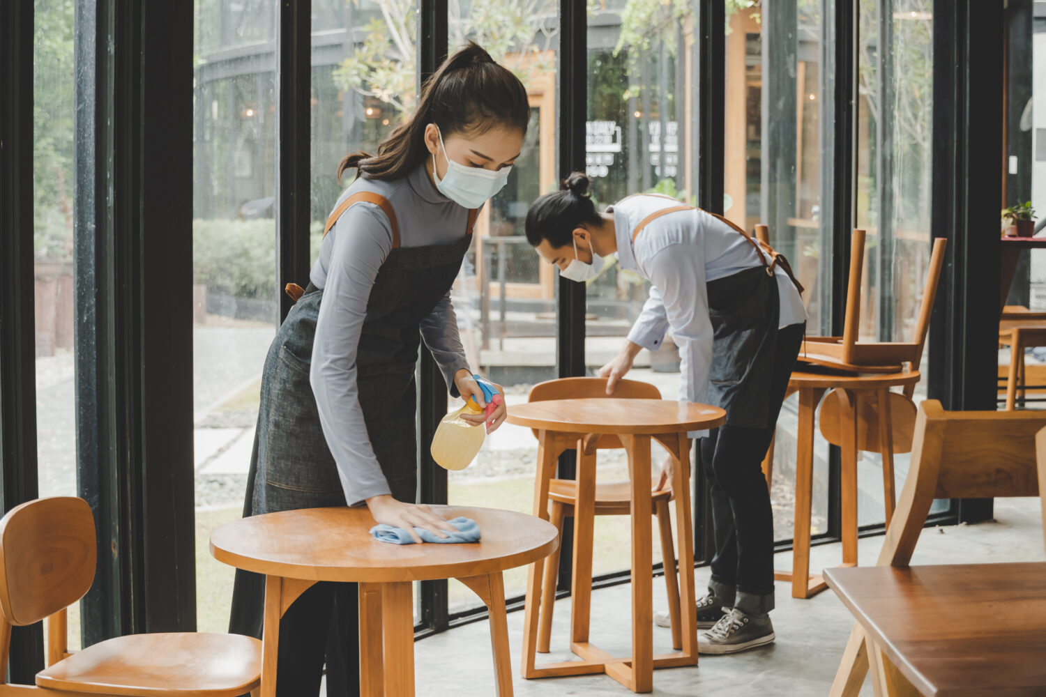 staff cleaning tables wearing face masks