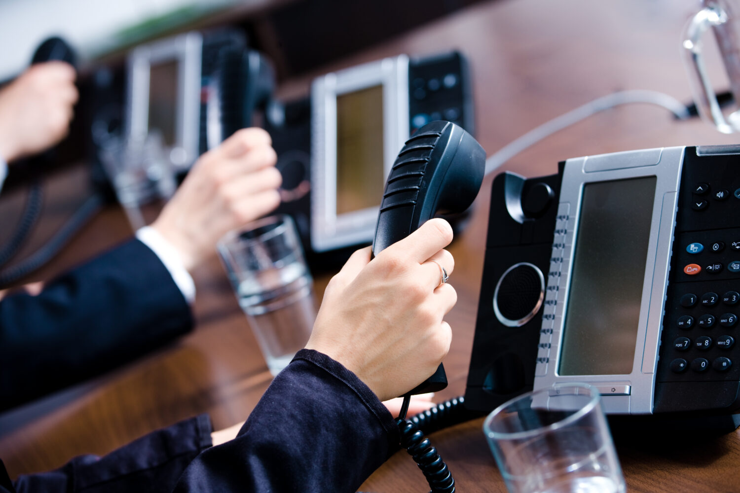 Close-up of hands holding landline phone receivers