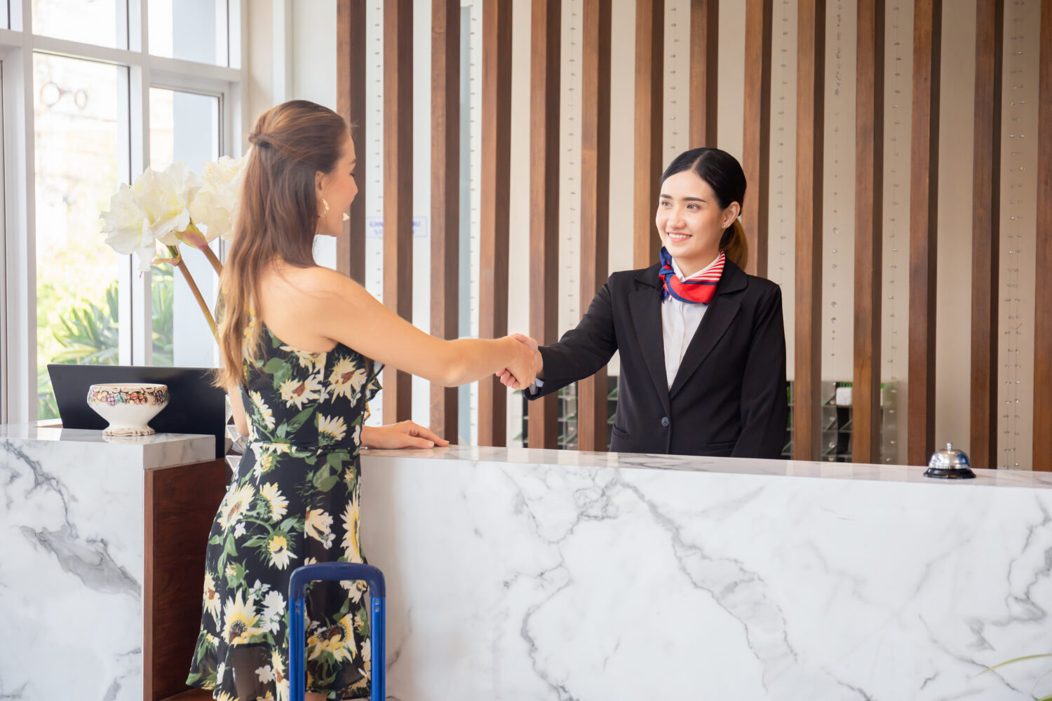 happy guest shaking hand with front desk receptionist
