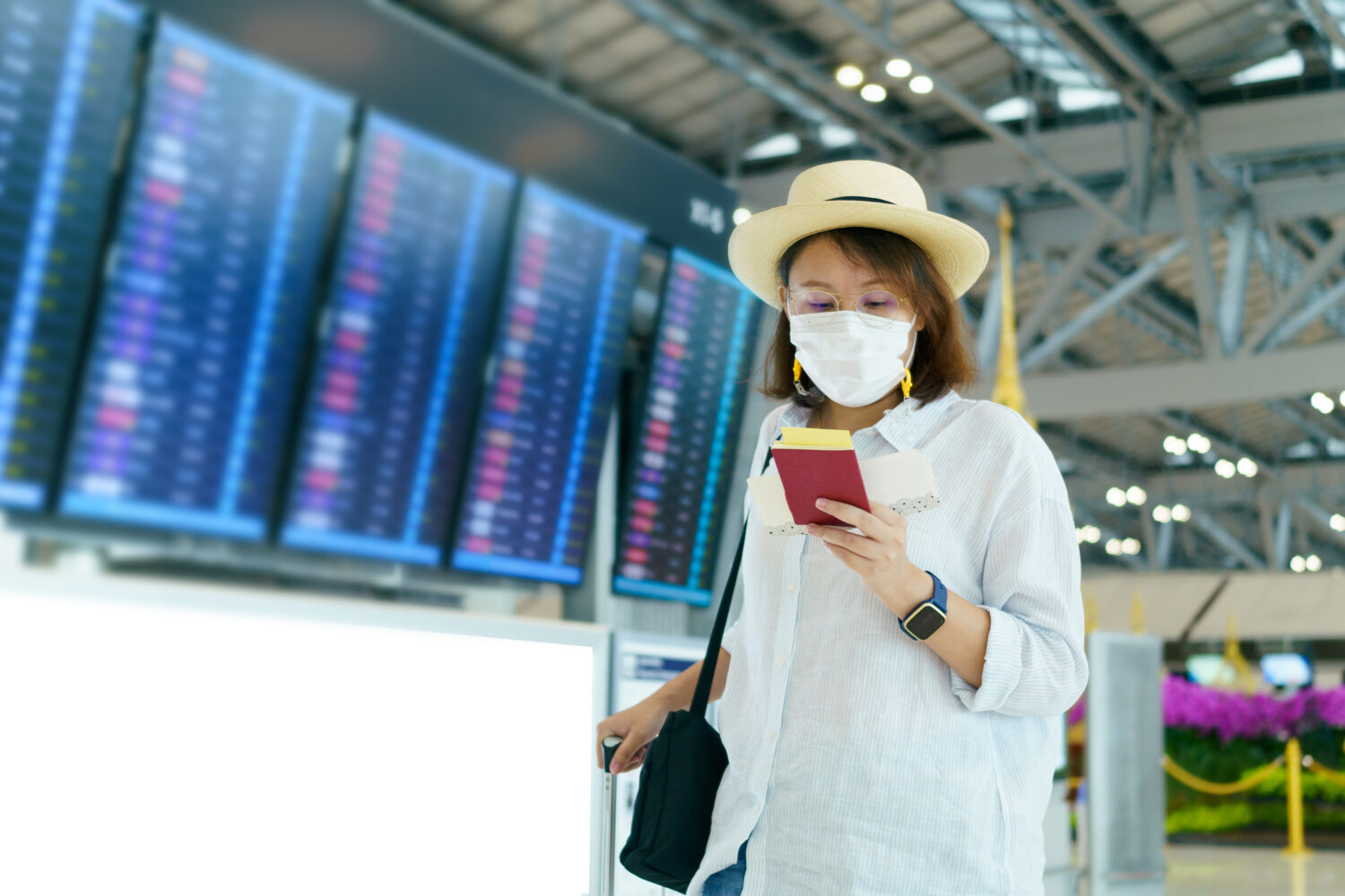 woman in a mask in airport terminal looking down at her phone