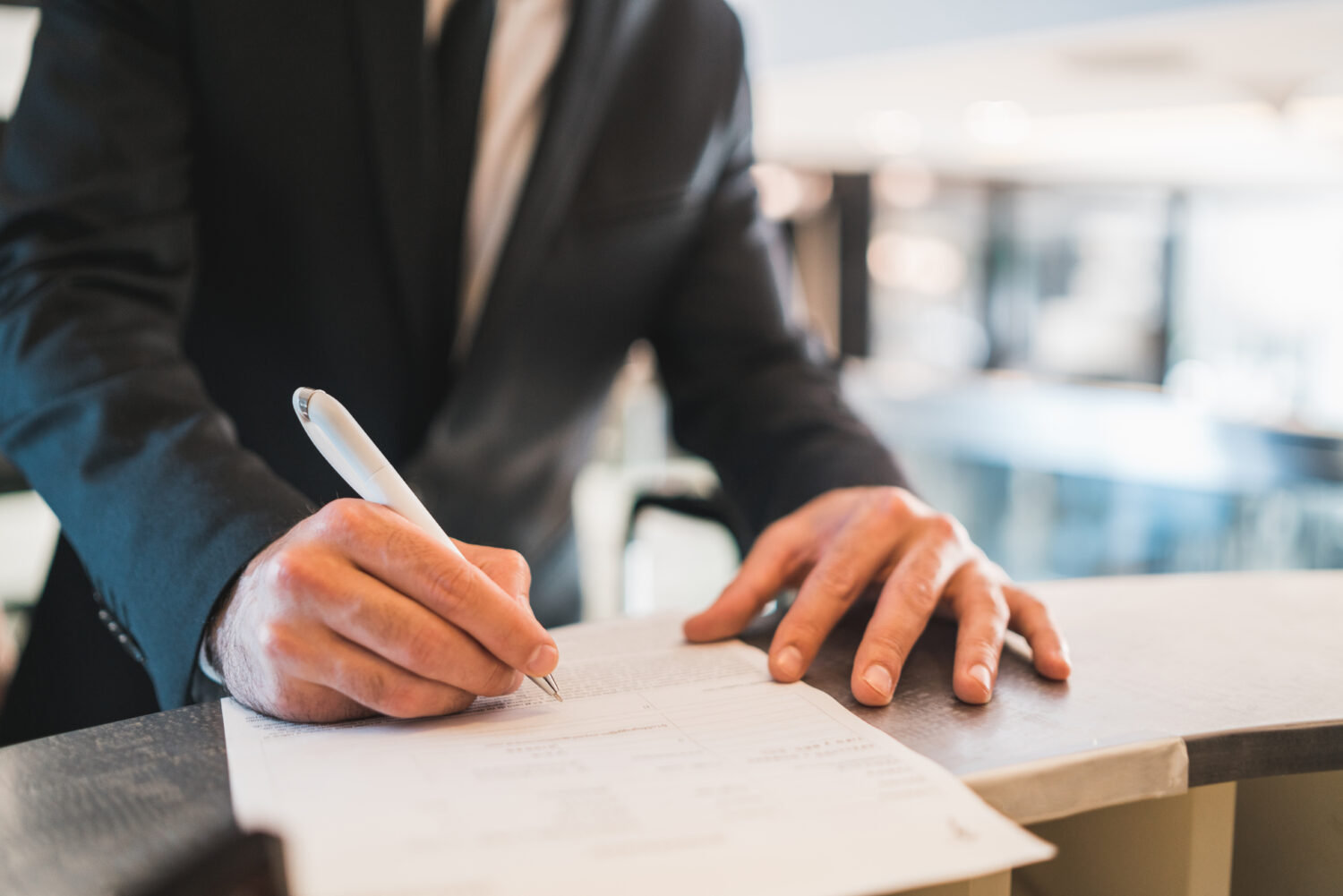 cropped image of businessman writing on papers at the front desk