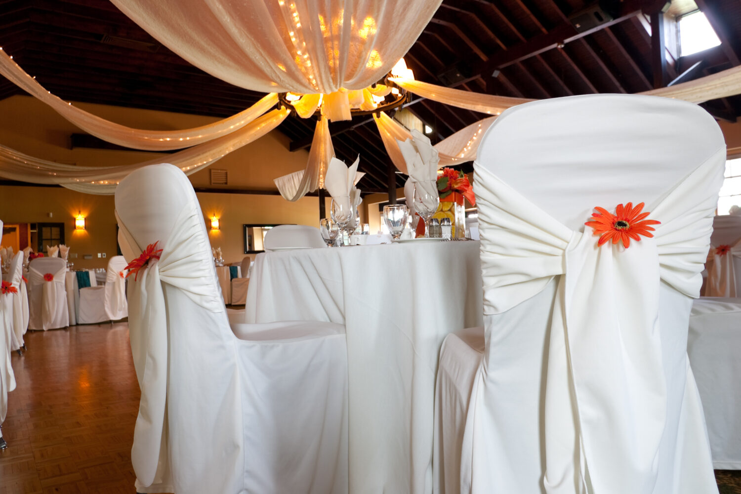 wideangle of a wedding venue focus on a single table with white covered chairs